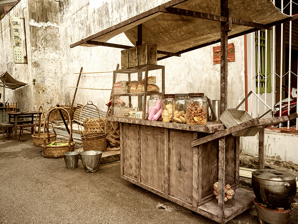 A little vegetable seller was displaying his goods next to a noodle stall.
