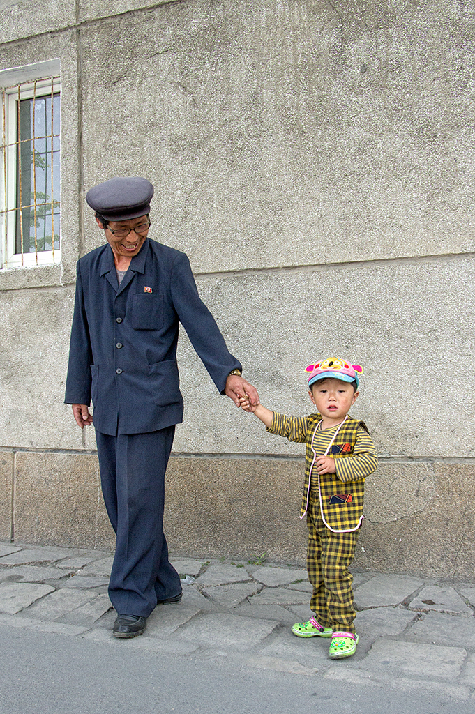 A grandpa taking his grandson for a morning stroll. There are no restrictions to the number of children each family can have. In fact, producing children is encouraged since DPRK is predominantly an agriculture country.