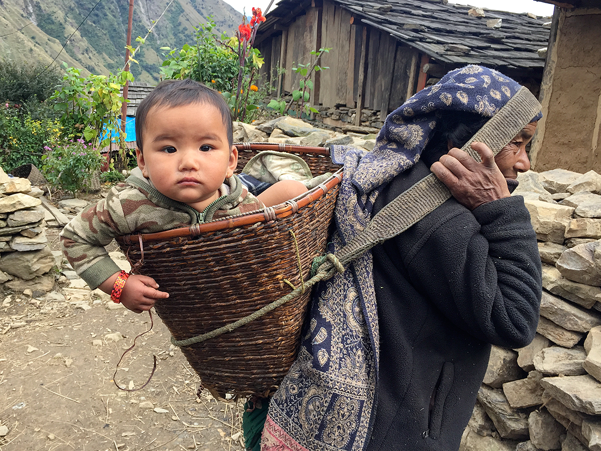 A mum carrying her baby in the old Laprak village